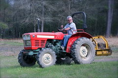 Man steering a tractor. Man driving a small tractor, hauling dirt Stock Photography