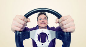 Man with a steering wheel, front view. Driver car concept.  Royalty Free Stock Photos