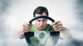 Man with a steering wheel in smoke, auto concept Royalty Free Stock Photo
