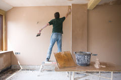 Man on step stool plastering wall in house under construction Royalty Free Stock Images