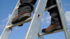Man on a stepladder. Detail of a man standing on aluminium stepladder Royalty Free Stock Image