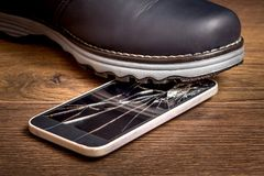 The man stepped on a cell phone and damaged the glass. Hacked mobile phone_. The man stepped on a cell phone and damaged the glass. Hacked mobile phone stock images