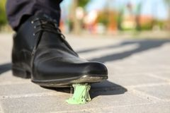 Man stepping in chewing gum on sidewalk. Concept of stickiness Stock Photography