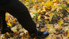 Man stepping on dead yellow leaves, autumn season. Colors in park, legs moving stock video