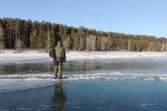Man stepping over a crack on thin ice of a frozen river Stock Image
