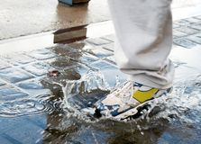 Man stepping into a water pool. Man stepping into a pool of water in a rush to get to his destination Stock Images
