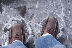Man steps on frozen puddle with thin ice Royalty Free Stock Photography