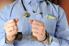 Man with stethoscope holds his hands in handcuffs before itself Royalty Free Stock Images