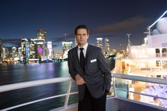 Man steward on ship board at night in miami, usa. Macho in suit jacket on city skyline. Water transport, transportation. Travellin. G for business. Wanderlust Royalty Free Stock Photo
