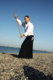 Man with stick exercising aikido Stock Images
