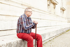 Man with stick sitting outdoor Royalty Free Stock Images