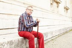 Man with stick sitting outdoor Stock Image