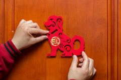 Man sticking a Chinese New Year of the Dog 2018 to door. Man sticking a Chinese New Year of the Dog 2018 to a door Royalty Free Stock Images