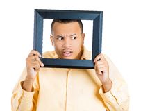 Man sticking head in picture frame Stock Photo