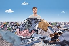 Man in a mess of laundry. A man is sticking his head out of a pile of clothing. The area around him is covered in clothing Royalty Free Stock Images