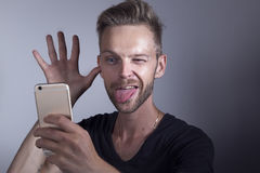 Man sticking out his tongue to phone. Funny man making funny faces to his mobile phone Stock Images