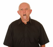 Man sticking out tongue. Bald middle aged man sticking out tongue, white studio background Stock Images