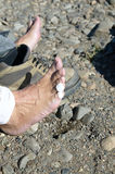 Man with sticking plaster on his toes. From his hiking boots sitting on stony ground viewed from above Stock Images