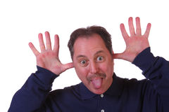 Man Sticking tongue out. Man with hands in his ears and tongue  sticking out making a funny face Stock Image