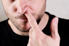 Man sticks a finger in his nose