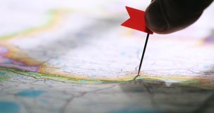 Man`s hand with a flag pin on the map is showing destination point. Travel concept. Man sticks flag pin on a map in necessary place to travel, hand closeup stock video