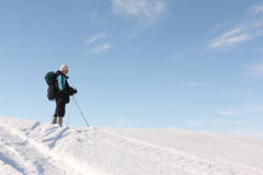 The man with sticks standing on a hilly surface of the frozen riveri. The man the traveler with a backpack and sticks standing on a hilly surface of the frozen stock photo