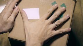 Man sticks a white sticker label to parcel carton box. Place for revealing text or logo. Man sticks a white sticker to parcel carton box stock footage