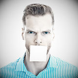 Man with sticky note over mouth Royalty Free Stock Images