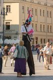 MAN ON STILTS. KRAKOW / POLAND: Main square and man on Stilts - Holiday tourist life of old town in the square Stock Image