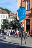 Man on stilts wielding a flag Stock Images