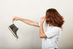 Man with stinky shoe. Young long haired man male wearing white t-shirt holding dirty stinky sweaty shoe in one hand fingers. Unpleasant smell stink stock images