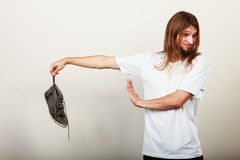 Man with stinky shoe. Young long haired man male wearing white t-shirt holding dirty stinky sweaty shoe in one hand fingers. Unpleasant smell stink royalty free stock photo