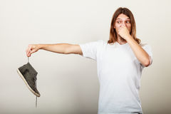 Man with stinky shoe. Young long haired man male wearing white t-shirt holding dirty stinky sweaty shoe in one hand fingers. Unpleasant smell stink royalty free stock photography