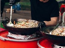Man stiring pasta with vegetables and seafood at street food festival. chef with gloves cooking traditional italian macaroni dis. H. open kitchen outdoors royalty free stock images