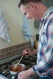 Man stirring food in pan at kitchen Royalty Free Stock Photo