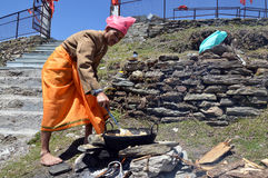 A man stirring halwa in kadhai. A man preparing halwa poori(puri) outdoors during tonsure(mundan) ceremony, Shimla, Himachal Pradesh, India Royalty Free Stock Images