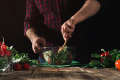 Man stirring salad of fresh vegetables on wooden table Royalty Free Stock Photography