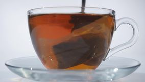 Man stirring tea with spoon in glass cup stock footage