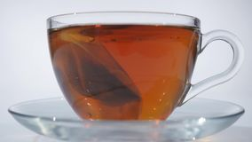 Man stirring tea with spoon in glass cup stock video