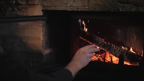 Man Stirs The Embers In The fireplace, Holiday And Lifestyle Concept stock footage