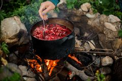 Man stirs food in a pan on campfire. Man stirs food in a black metal pan on campfire among rocks and grass stock photos