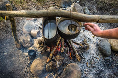 Man stirs ladle food that is prepared in a hike in the cauldrons Royalty Free Stock Images