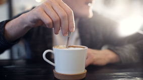 Man stirs sugar in a cup of coffee stock footage