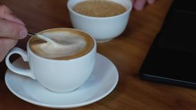 Man stirs sugar in a cup with coffee. on the table next to a laptop. stock footage