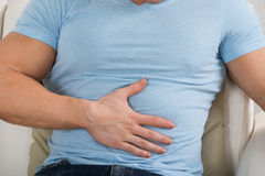 Man With Stomach Ache Sitting On Couch Stock Photography