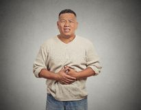 Man with stomach pain. Closeup portrait miserable upset man, person doubling over in acute body stomach pain, looking very sick isolated grey wall background Stock Photo