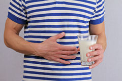 Man with stomach pain holding a glass of milk. Dairy Intolerant person. Lactose intolerance, health care concept. Royalty Free Stock Image