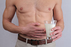 Man with stomach pain holding a glass of milk. Dairy Intolerant person. Lactose intolerance, health care concept. Stock Image