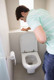 Man with stomach sickness about to vomit into the toilet. Rear view of a young man with stomach sickness about to vomit into the toilet Royalty Free Stock Photo