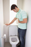 Man with stomach sickness about to vomit into the toilet. Side view of a young man with stomach sickness about to vomit into the toilet Stock Photo